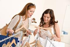Fashion shopping - two happy woman choose sale clothes Stock Photos