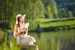 Stock Photo of long red hair romantic woman relax by lake with book