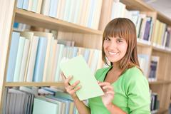 student in library - cheerful woman choose book - stock photo