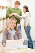 high school library - happy student with laptop - stock photo