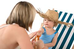 Mother with child apply suntan lotion on beach Stock Photos