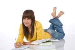 student - happy female teenager write homework - stock photo