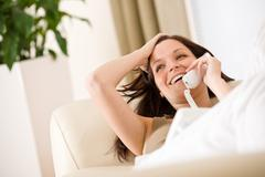 Stock Photo of on the phone home: smiling woman lying down on sofa calling