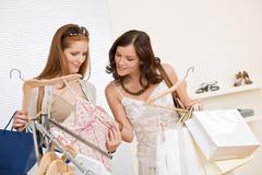 fashion shopping -  two happy young woman choose clothes - stock photo