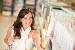 Shopping cosmetics - smiling woman choose shampoo Stock Photos