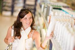 shopping cosmetics - smiling woman choose shampoo - stock photo