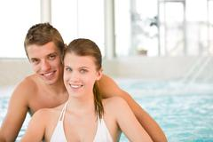swimming pool - young cheerful couple have fun - stock photo