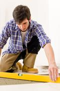 home tile improvement - handyman with level - stock photo