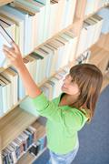 student in library - happy woman choose book - stock photo
