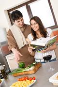smiling couple in modern kitchen cook together - stock photo