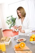 breakfast - happy woman with toast and marmalade - stock photo