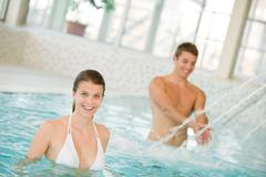 Swimming pool - young couple have fun under water stream Stock Photos