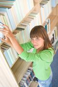 Student in library - happy woman search for book Stock Photos