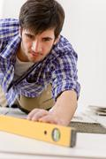 Home tile improvement - handyman with level Stock Photos