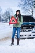 winter car breakdown - woman warning triangle - stock photo