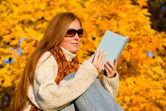 Stock Photo of autumn sunset country - woman read book