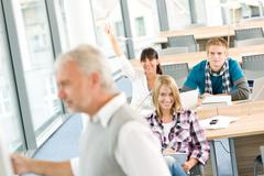 high school - three students with mature professor - stock photo