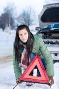 Winter car breakdown - woman warning triangle Stock Photos