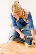 home improvement - handywoman sanding wooden floor - stock photo