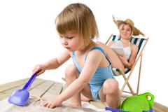 beach - mother with child playing with toys in sand - stock photo