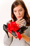 Stock Photo of surprised woman holding present shoes