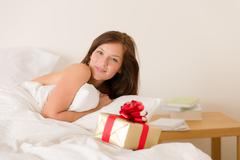 Stock Photo of bedroom surprise present - young happy woman