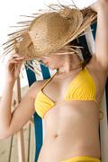Stock Photo of beach - woman with straw hat in yellow bikini sunbath