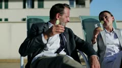 Happy business couple with drinks relaxing on sunbeds Stock Footage