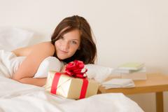 bedroom surprise present - young happy woman - stock photo