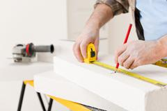 Home improvement - handyman measure porous brick Stock Photos