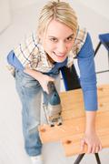 home improvement - handywoman cutting wooden floor - stock photo