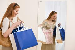 Fashion shopping - happy woman try on sale clothes Stock Photos