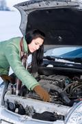 winter car breakdown - woman repair motor - stock photo