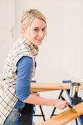 home improvement - handywoman painting wooden plank - stock photo
