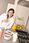 young woman having breakfast in modern kitchen - stock photo
