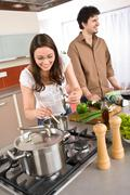 Young couple cooking together in modern kitchen Stock Photos