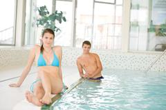 Swimming pool - young couple relax on poolside Stock Photos