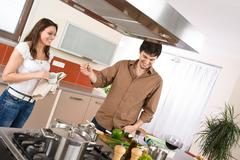 Happy couple in modern kitchen with red wine Stock Photos