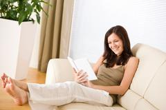 Stock Photo of young happy woman read book on sofa
