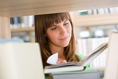 student in library - happy woman read book - stock photo