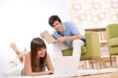 student - two teenager with laptop in living room - stock photo