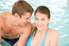 Young loving couple have fun in swimming pool Stock Photos