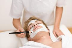 male cosmetics - facial mask in salon - stock photo