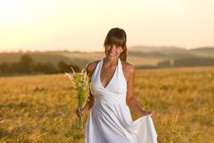 Stock Photo of romantic woman in sunset corn field wear dress