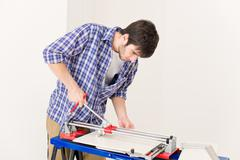 Home improvement - handyman cut tile Stock Photos
