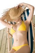 Stock Photo of beach - woman with straw hat in yellow bikini