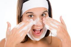 teenager problem skin care - woman wash face - stock photo