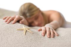 beach - woman with starfish lying in sand - stock photo