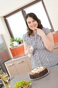 happy plus size woman with chocolate cake and cream in kitchen - stock photo