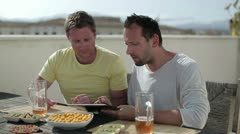 Male friends with tablet computer drinking beer on the terrace Stock Footage